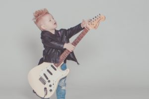 Photo of a year old with a mohawk and leather jacket playing guitar.