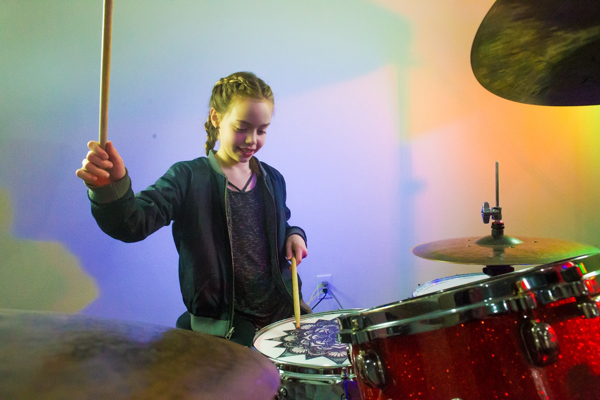 A girl playing a big red drum set at Backbeat music Academy in Portland, OR