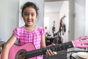 A girl in a pink short playing a pick guitar with stickers to mark every C on the fretboard