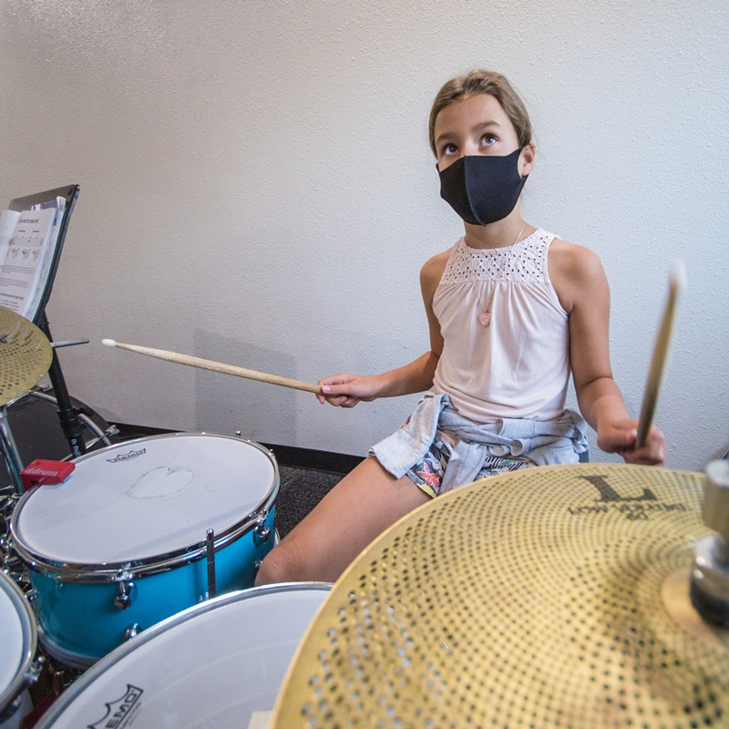 A girl playing the drums during drum lessons in Portland OR