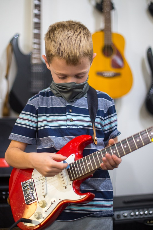 A boy playing the guitar with a face mask on during coronavirus times at Backbeat Music Academy