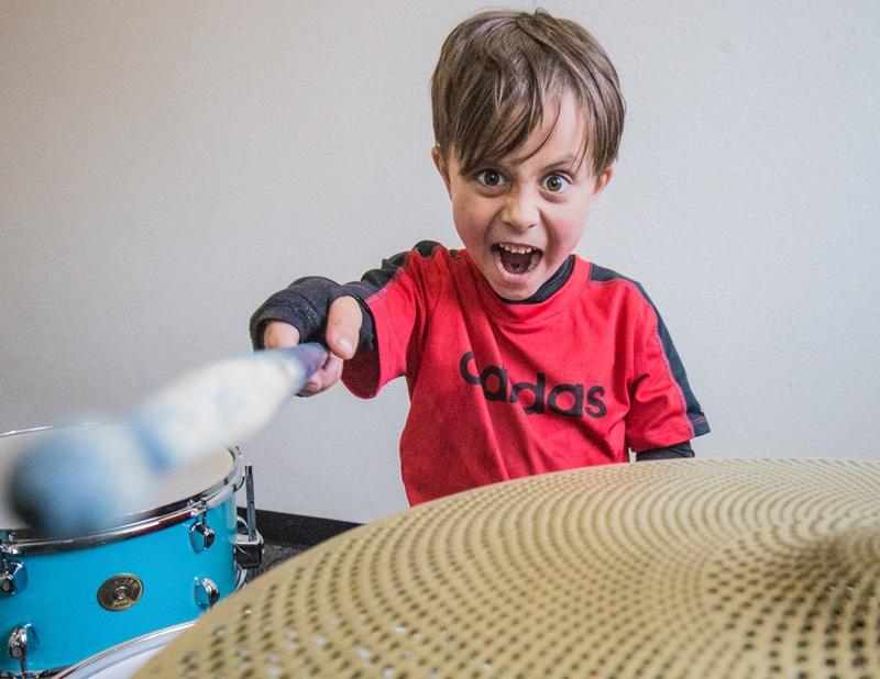 A boy making an awesome face while playing drums